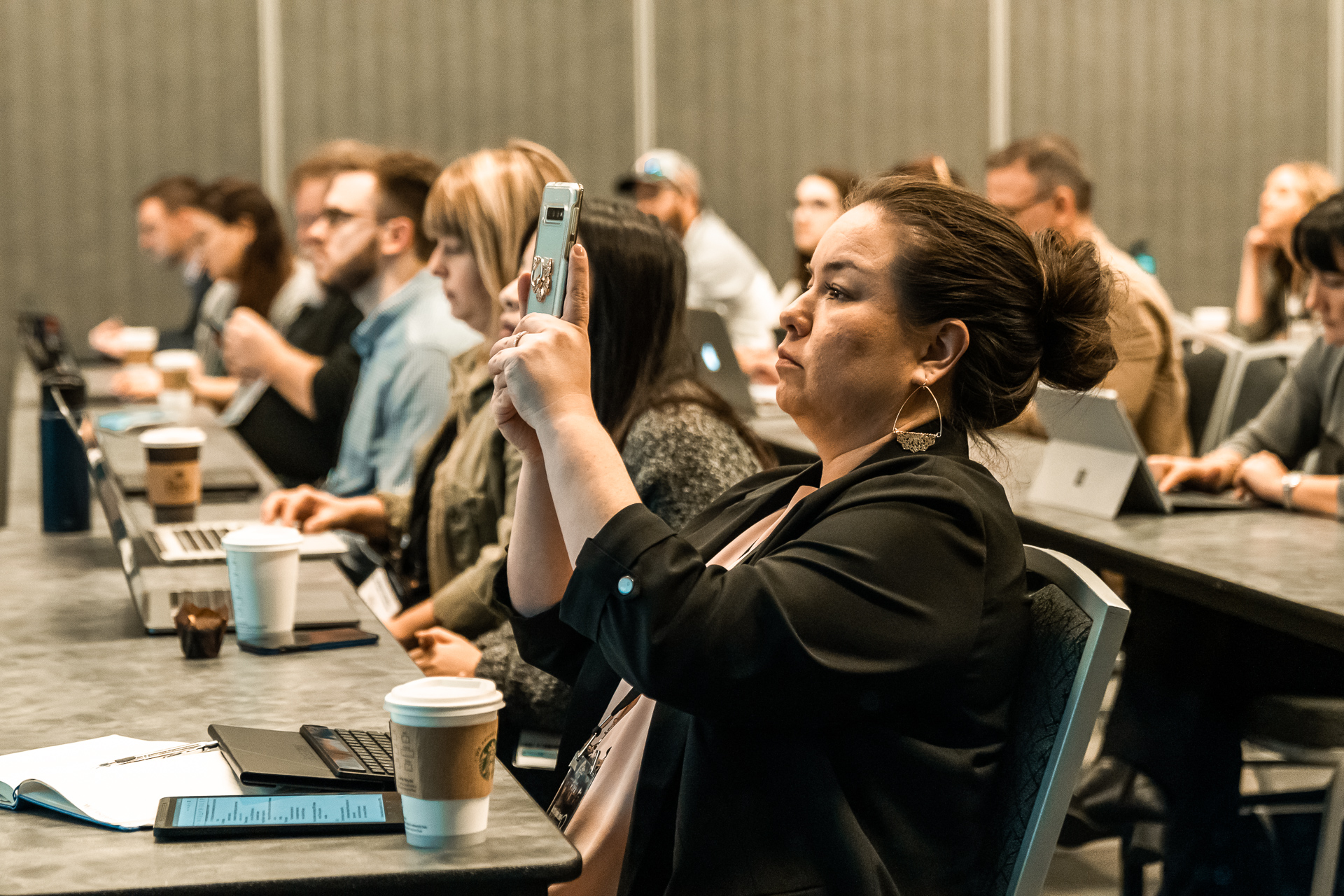 Lady at a conference capturing a photo of the speaker